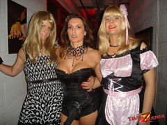 These two sexy blonde crossdressers get seduced by a gorgeous femdom with a big strapon outside a fetish club
